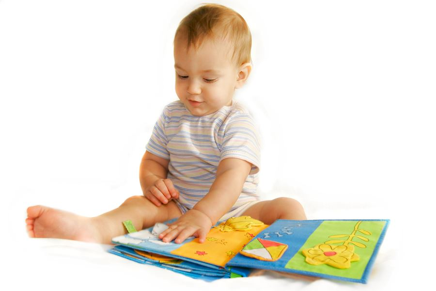 Toddler boy reading a book.